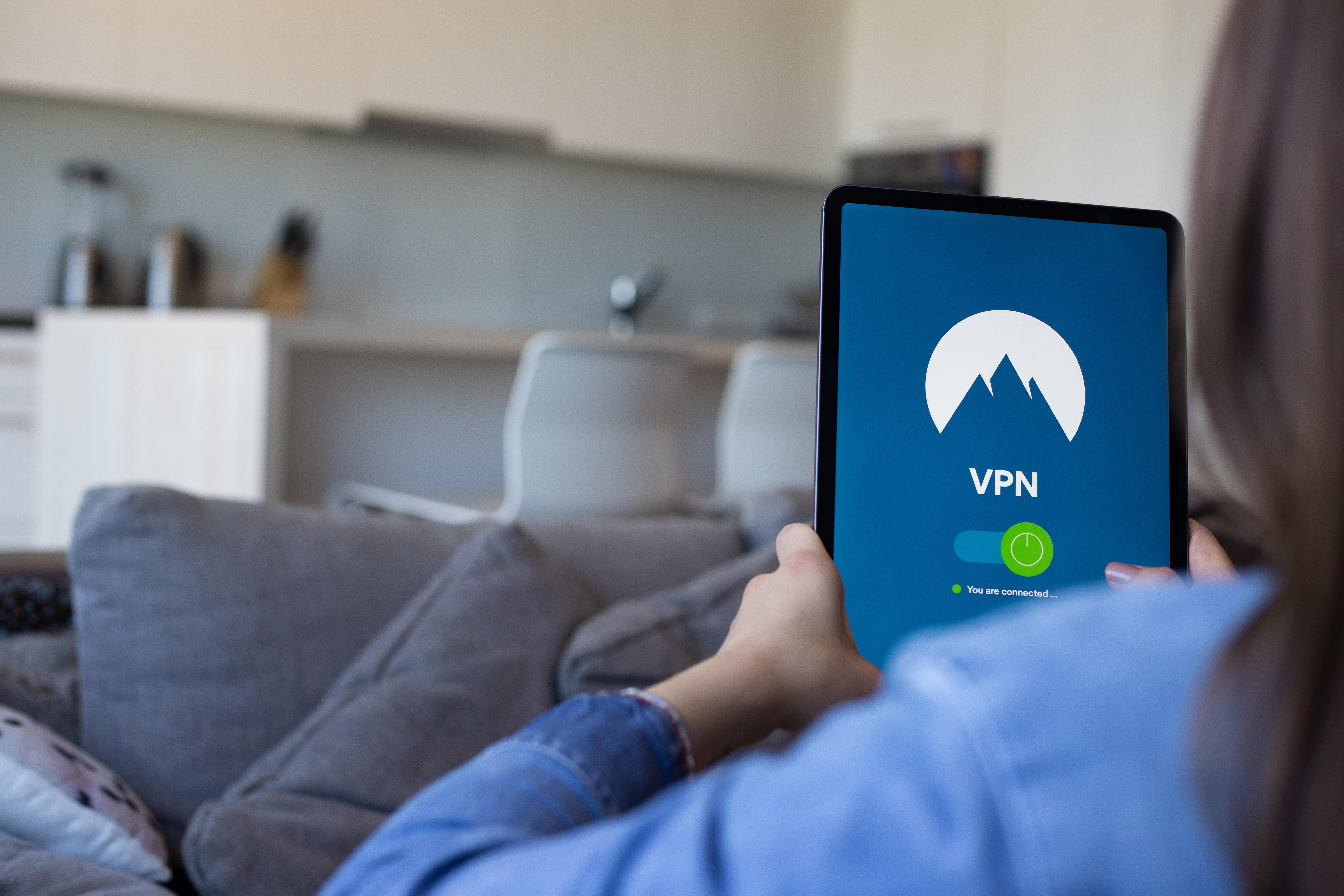 ภาพของผู้หญิงกำลังนั่งอยู่บนโซฟาใช้แท็บเล็ต อยู่ในหน้าจอเปิด VPN