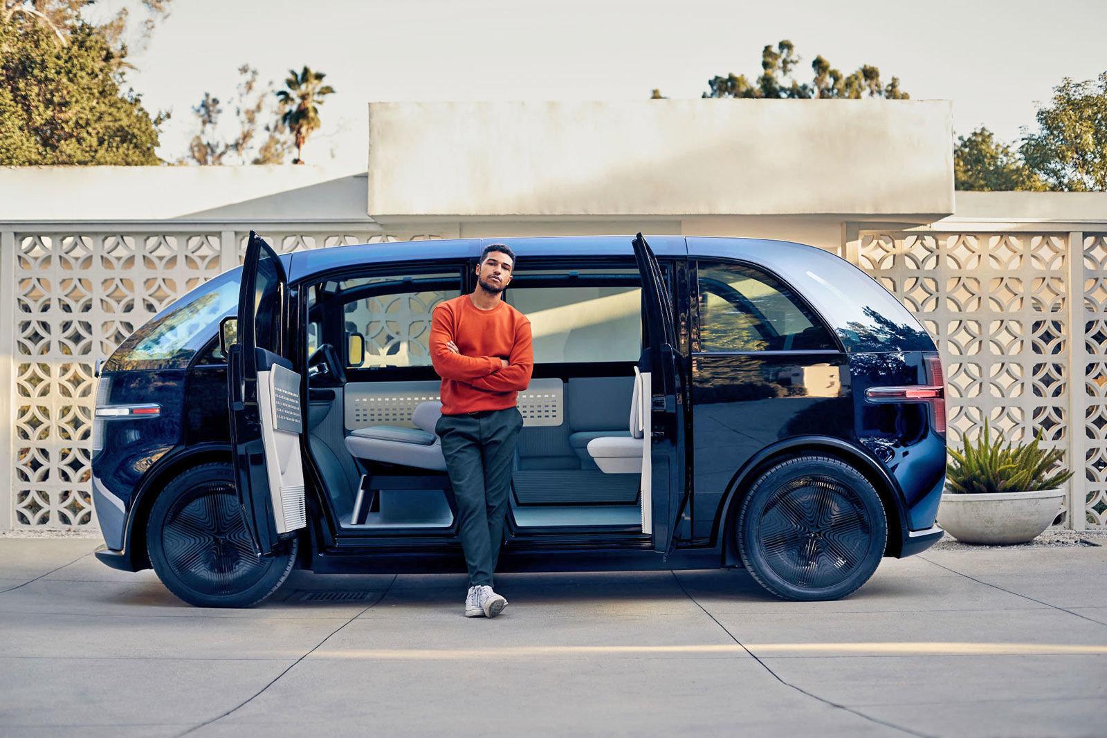 ผู้ชายใส่เสื้อแขนยาวสีส้ม กางเกงสีเขียว รองเท้าผ้าใบสีขาว กำลังยืนกอดอกอยู่ข้างรถตู้สีดำ Canoo ที่เปิดประตูอยู่