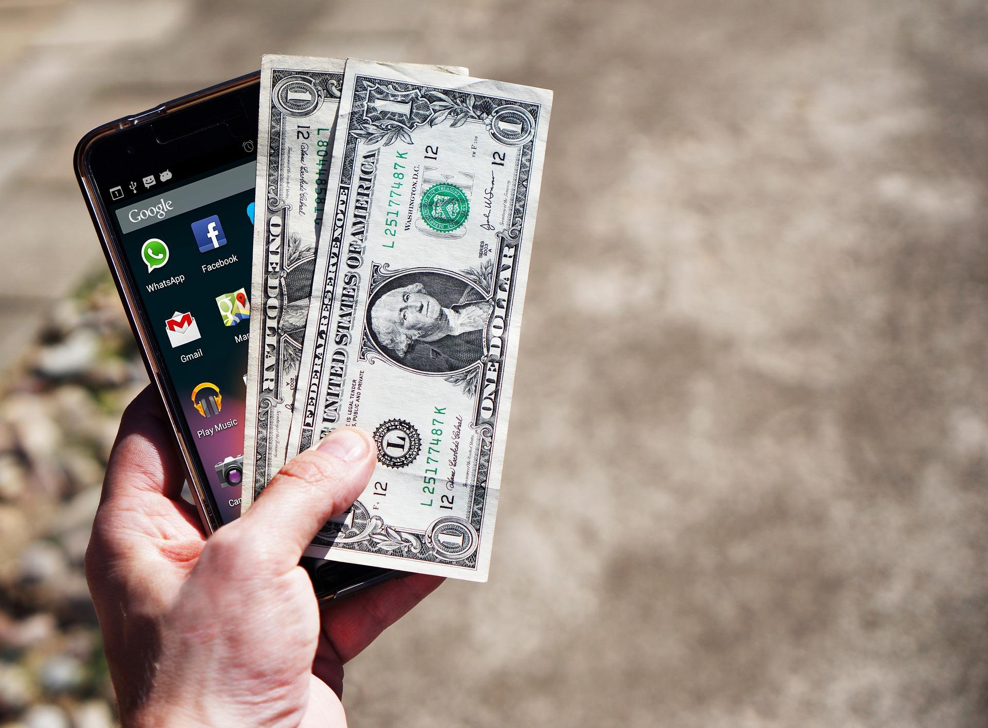 มือข้างซ้ายกำลังถือสมาร์ทโฟน และเงินสองดอลล่าห์สหรัฐ