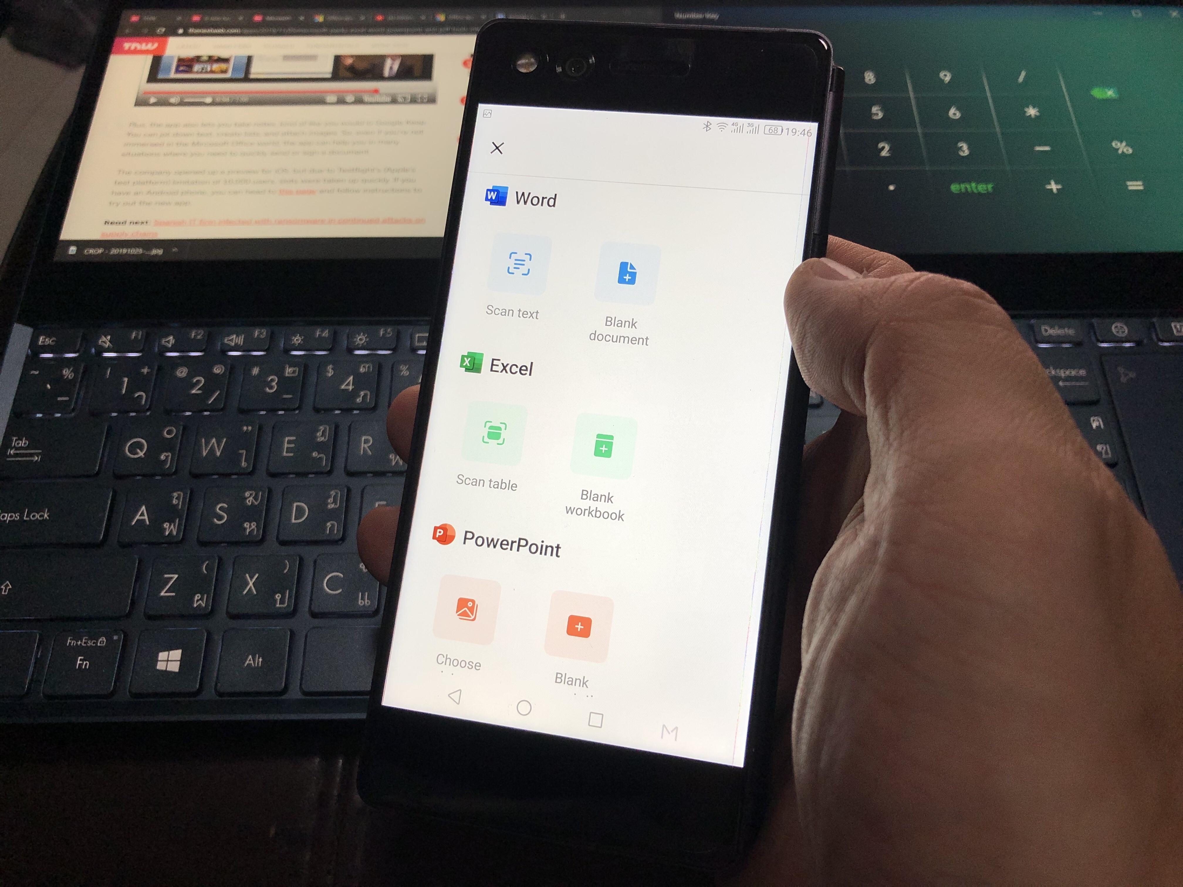 มือข้างขวากำลังถือสมาร์ทโฟนสีดำ เปิดแอป Office อยู่ มีแบ็กกราวด์เป็นโน้ตบุ๊ก